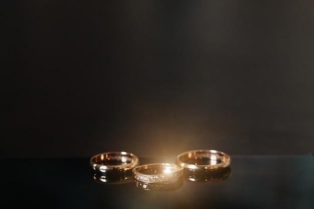 Gouden trouwringen liggen op een houten tafel