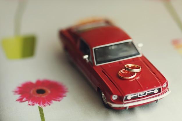 Gouden trouwringen liggen op een speelgoed rode mustang
