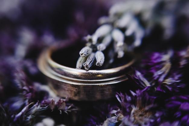 Gouden trouwringen liggen op het bouquet van violette lavendel