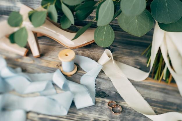 Gouden trouwringen met beige schoenen van de bruid en een spoel met lint op een groene ondergrond