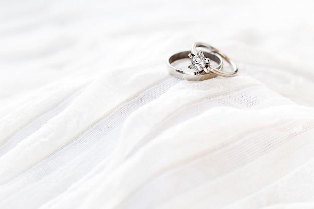 Gouden trouwringen met diamant liggen op witte stof. symbool van liefde en huwelijk.