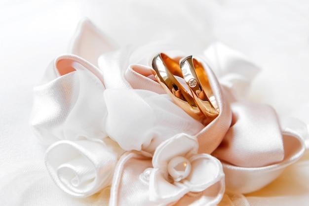 Gouden trouwringen met diamant op zijden rozen
