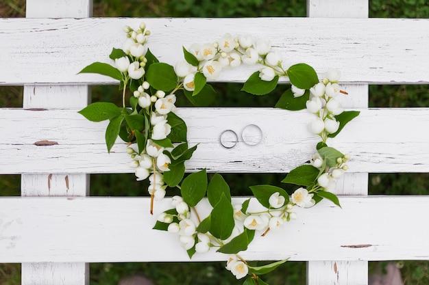 Gouden trouwringen met diamanten liggen in jasmijnbloem in bruidsboeket