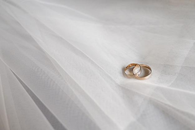 Gouden trouwringen met edelstenen op de sluier van de bruid.