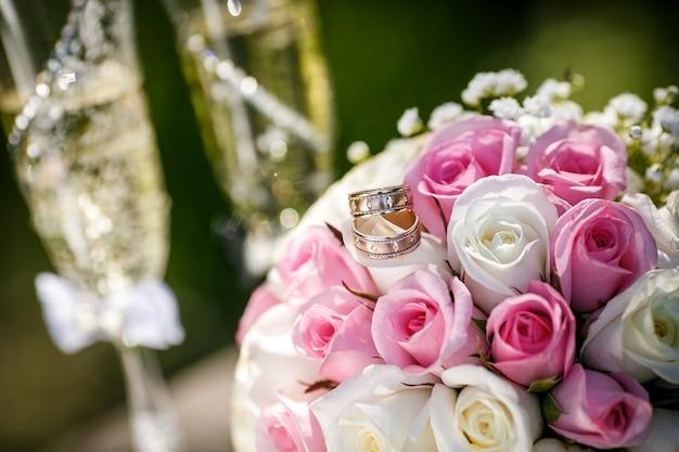 Gouden trouwringen met rozen en glazen champagne