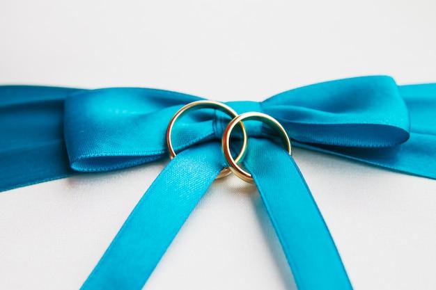 Gouden trouwringen op blauwe strik