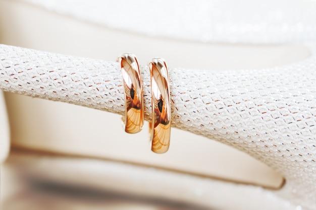 Gouden trouwringen op bruidschoenen met bergkristallen. bruiloft sieraden details. symbool van liefde en huwelijk.