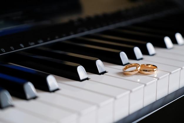 Gouden trouwringen op de piano toetsen.