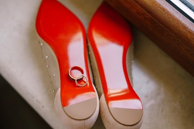 Gouden trouwringen op de rode zool van balletschoenen voor de bruid op de vensterbank