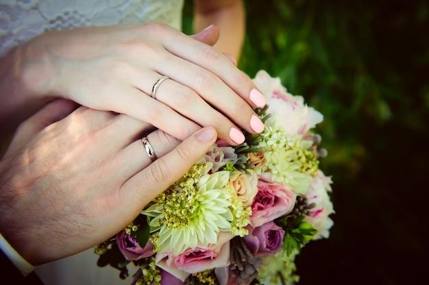 Gouden trouwringen op de vinger van bruid en bruidegom