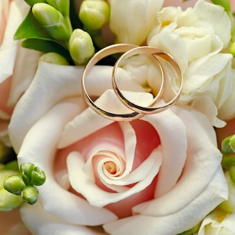 Gouden trouwringen op een boeket bloemen voor de bruid