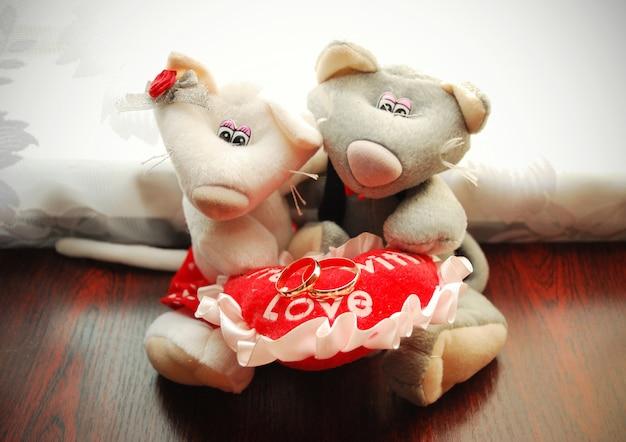 Gouden trouwringen op een hart vastgehouden door souvenir zachte muizen
