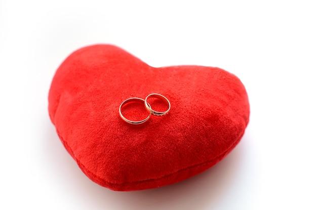 Gouden trouwringen op een speelgoed decoratief rood hart