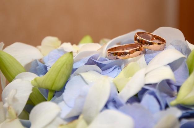 Gouden trouwringen op een witte bloem van een mooi bruidsboeket met paarse bloemen close-up