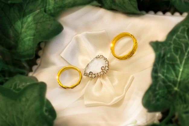 Gouden trouwringen op het kussen. bruiloft symbolen, attributen. feestelijke achtergrond. macrofoto. vervagen