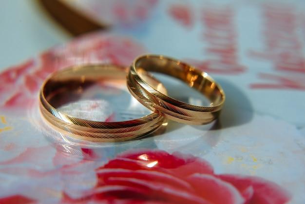Gouden trouwringen op tafel, onscherpe achtergrond. trouwringen met een geribbeld oppervlak, close-up.