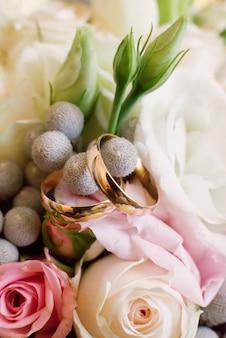 Gouden trouwringen op verse bloemen in het boeket van de bruid. bruiloft details