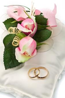 Gouden trouwringen op witte kussen met roos