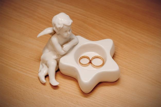 Gouden trouwringen voor de bruid en bruidegom liggen op een souvenirengel met een ster