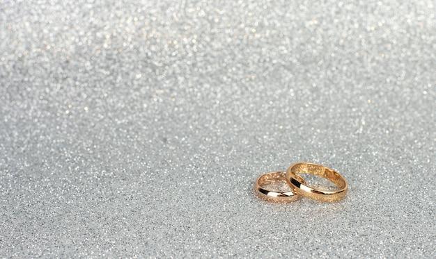 Gouden trouwringen voor pasgetrouwden op een zilveren achtergrond met bokeh close-up
