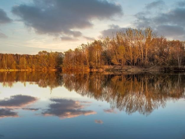 Gouden uurzonlicht bij bosmeer met stilstaand wateroppervlak dat wolken en kale bomen weerkaatst op de verre kust in de lenteavond