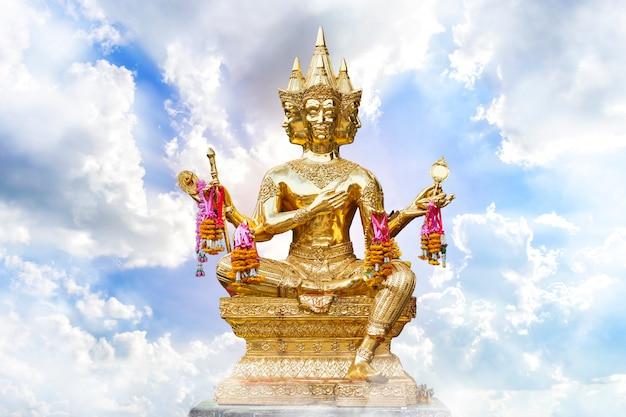 Gouden van brahma-standbeeld godsdienstig met blauwe hemel met witte vlokschuim zeer wolkenachtergrond van thailand.