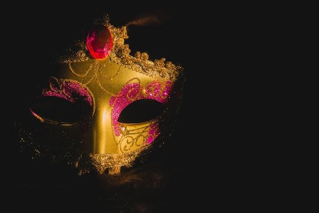 Gouden venetiaans masker op een zwarte achtergrond