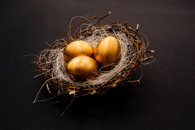 Gouden verfraaide eieren van pasen op donkere achtergrond.