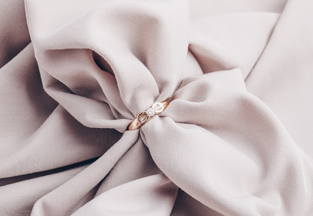 Gouden verlovingsring met diamant op beige achtergrond
