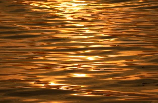 Gouden wateroppervlak met reflecties van het zonlicht