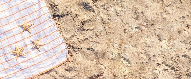 Gouden zeester op een sprei op een zandstrand. bovenaanzicht, plat gelegd. banier.