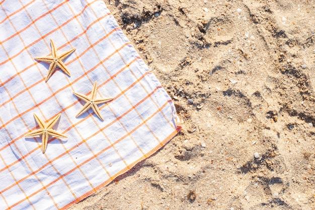 Gouden zeester op een sprei op een zandstrand. bovenaanzicht, plat gelegd.