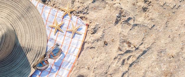 Gouden zeesterren, hoed, bril op het zandstrand. bovenaanzicht, plat gelegd. banier.