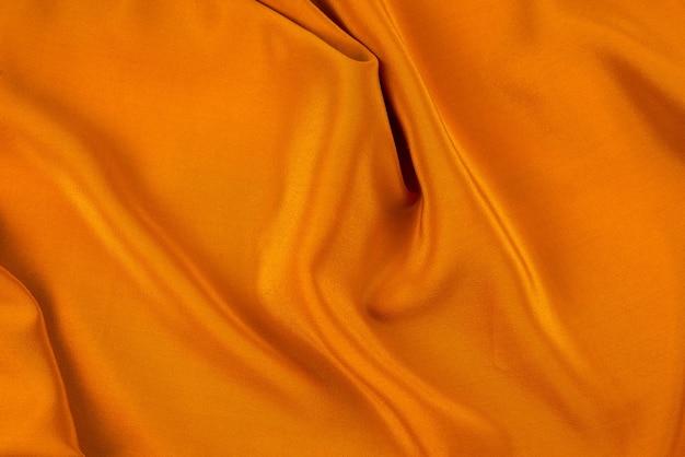 Gouden zijde of satijn luxe stof textuur kan als abstracte achtergrond gebruiken. bovenaanzicht.