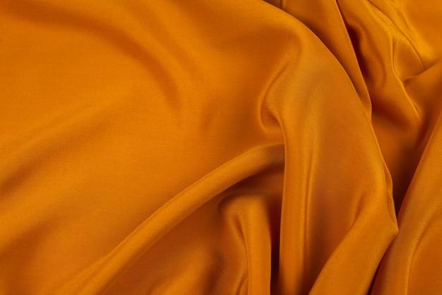 Gouden zijde of satijn luxe stof textuur kan als abstracte achtergrond gebruiken