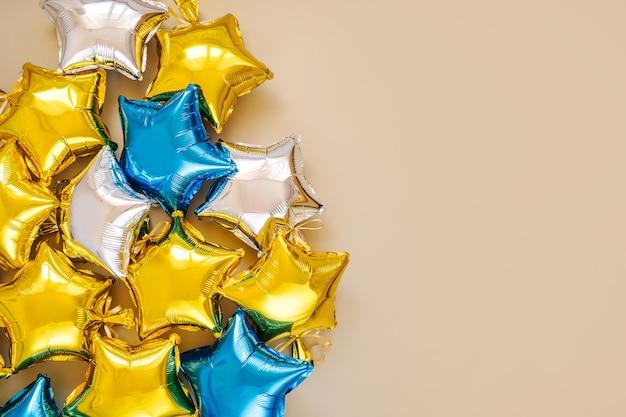 Gouden, zilveren en blauwe folieballonnen in de vorm van een ster. vakantie en viering concept. verjaardagsdag of feestdecoratie. metalen luchtballonnen. gefeliciteerd. wenskaart.