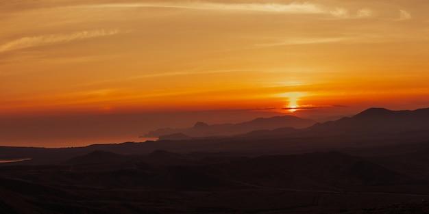 Gouden zonsondergang in bergen aan zee