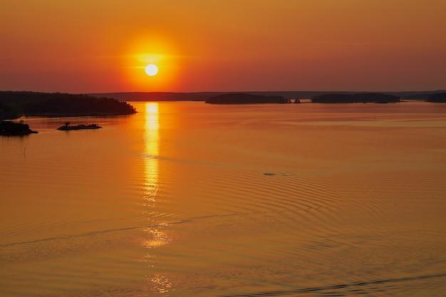 Gouden zonsondergang in naantali, finland. weerspiegeling van de zon op het water. kopieer ruimte.
