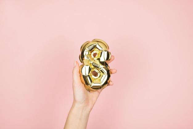 Goudfolie ballonnen cijfer 8 in vrouwelijke hand op roze oppervlak. fijne vrouwendag