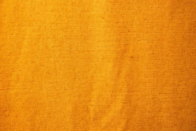 Goudgeel, achtergrond van textiel met patroon, close-up.
