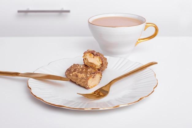Goudkleurige eclairs op plaat mes en vork kopje koffie