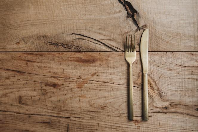goudkleurige rvs bestekset van mes en vork op een authentiek ruwhouten tafelblad met ruimte voor tekst