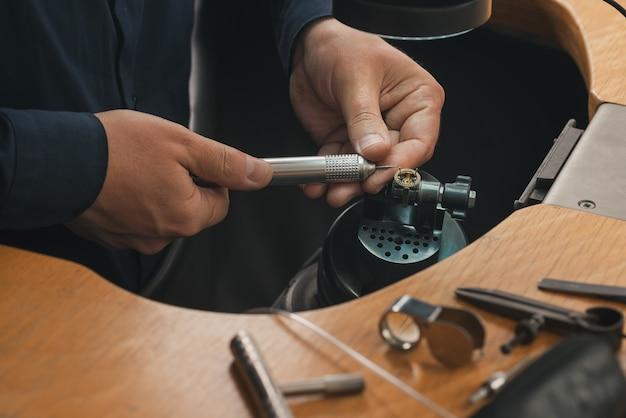 Goudsmid aan het werk. juwelierswerkbank met verschillende gereedschappen. desktop voor het maken van sieraden met professionele gereedschappen.