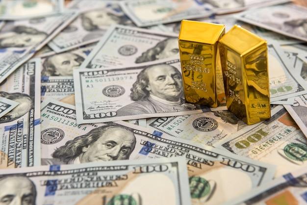 Goudstaven die op dollarbiljetten liggen. geld en concept opslaan