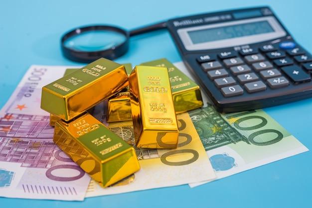 Goudstaven, eurobankbiljetten, rekenmachine en vergrootglas op een blauwe tafel.