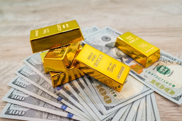 Goudstaven op amerikaanse dollarbiljetten, financieel besparingsconcept