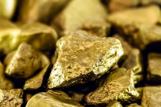 Goudstenen, ruwe goudklompjes op zwart oppervlak.