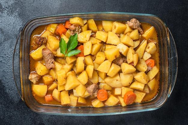 Goulashvlees met aardappelen, gestoofde groenten en varkensvlees