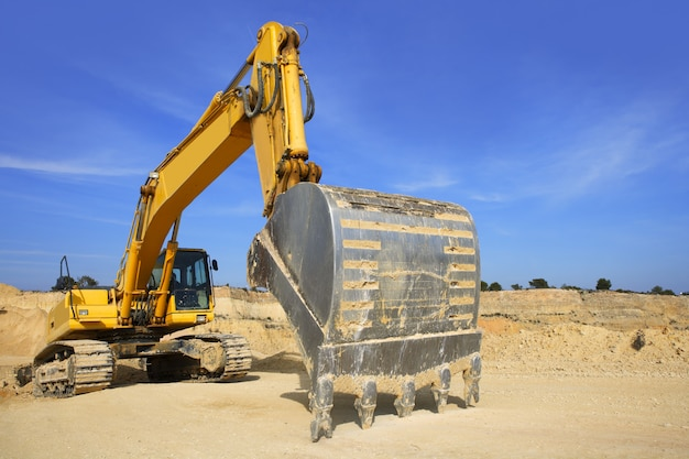 Graafmachine gele voertuig zandgroeve buiten blauwe hemel
