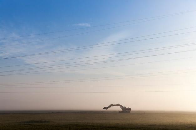 Graafmachine staat op het gebied van werkzaamheden ter plaatse die 's ochtends van de dag in de mist worden uitgevoerd